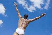 Semi-nude African man with arms outstretched — Stock Photo