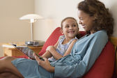 African mother reading to daughter — Stock Photo