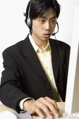 Asian businessman wearing headset at desk — Stock Photo