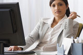 Indian businesswoman sitting at desk — Stock Photo