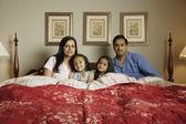 Familia india sentado en la cama — Foto de Stock