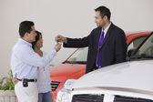 Hispanic couple taking keys from car salesman — Stock Photo