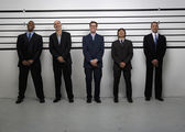 Multi-ethnic businessmen in police line up — Stock Photo