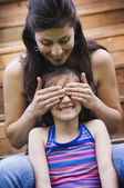 Hispanic mother covering daughter's eyes — Stock Photo