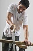 Homem hispânico serrar a placa de madeira — Foto Stock