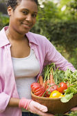 African woman carrying basket of fresh vegetables — Stock Photo