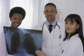 Multi-ethnic doctors and patient looking at x-ray — Stock Photo