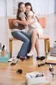 Niñas hispanas abrazando en zapatería — Foto de Stock