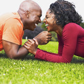 African couple laughing in grass — Stok fotoğraf