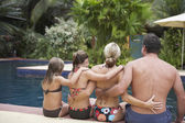 Family sitting arm in arm next to swimming pool — Stock Photo