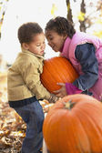 African brother and sister lifting pumpkin — Zdjęcie stockowe