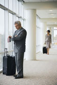 Hispanic businessman next to suitcase — Stockfoto