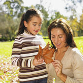 Hispanic mother and daughter looking at autumn leaf — Stock Photo