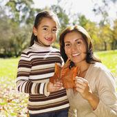 西班牙裔美国人的母亲和女儿看着秋天叶 — 图库照片