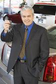 Hispanic car salesman holding car keys — Stock Photo