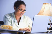 African businesswoman working in pajamas — Stock Photo
