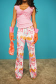 Young woman wearing rubber gloves and pajamas — Stock Photo
