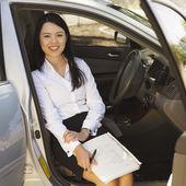 Eurasian businesswoman sitting in car — Stock Photo