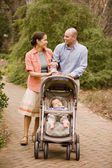 Hispanic parents pushing baby in stroller — Stock Photo