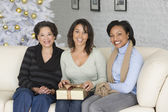 African mother and adult daughters with Christmas gift — Stock Photo