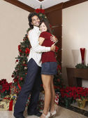 Hispanic couple hugging next to Christmas tree — Стоковое фото