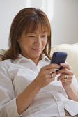Asian woman looking at cell phone — Stock Photo