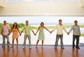 Multi-ethnic friends holding hands at beach resort — Stock Photo
