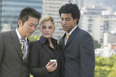 Three businesspeople looking at cell phone — Stock Photo