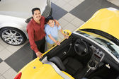 Hispanic father and son next to new car — Stock Photo
