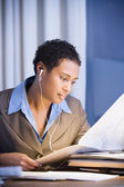African businesswoman reading newspaper — Stock Photo