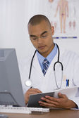 Male doctor writing in notebook — Stock Photo