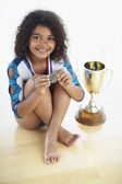 Young female gymnast with medal and trophy — Stock Photo