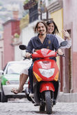 Hispanic couple on scooter — Stock Photo