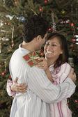 Casal latino-americanos abraçando no natal — Fotografia Stock