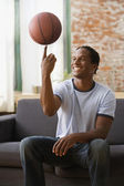 African man spinning basket ball on finger — Stock Photo