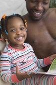 Padre africano lettura alla figlia — Foto Stock