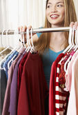 Hispanic woman next to rack of clothing — Stock Photo