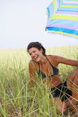 Woman laughing under beach umbrella — Stock Photo
