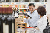 Hispanic couple looking at wine — 图库照片