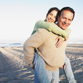 Hispanic man giving wife piggyback ride at beach — Stock Photo