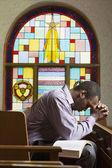 Afryki amerykański człowiek modli się w kościele — Zdjęcie stockowe