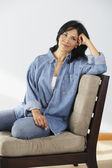 Hispanic woman sitting on chair — Stock Photo