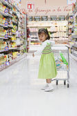 Hispanic girl pushing child's shopping cart — Stock Photo