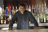 Hispanic male bartender leaning on bar — Stock Photo