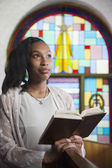 African American woman reading Bible in church — Stock Photo