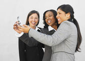 Multi-ethnic businesswomen looking at cell phone — Stock Photo