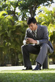 South American businessman sitting in park — Stock Photo