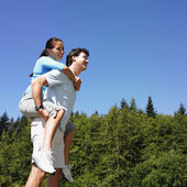 Man giving girlfriend piggy back ride — Stock Photo