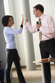 Businessman and businesswoman high-fiving — Stock Photo
