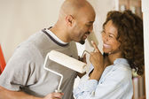 African couple being silly with paint rollers — Stock Photo